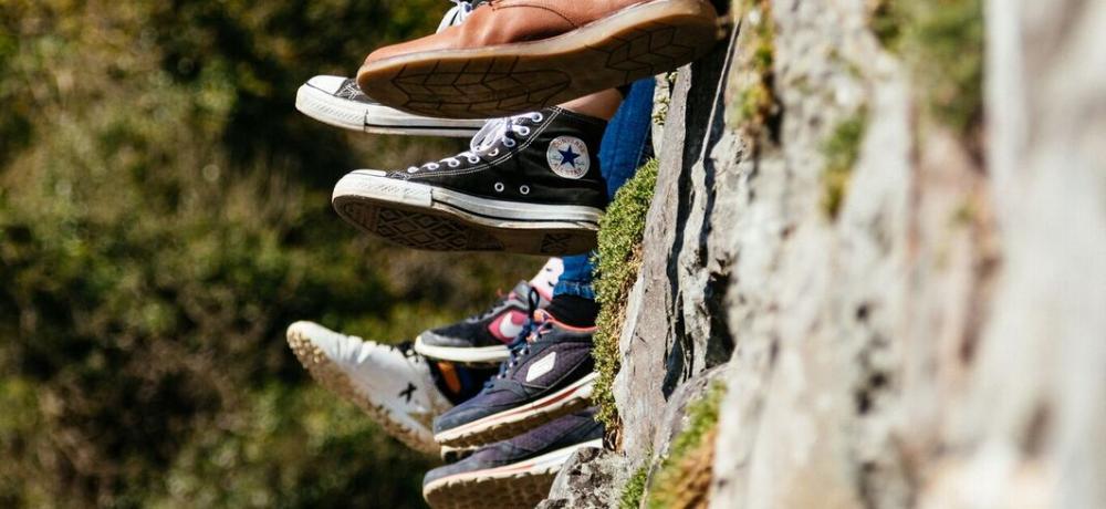 Fötter och skor mot bergvägg