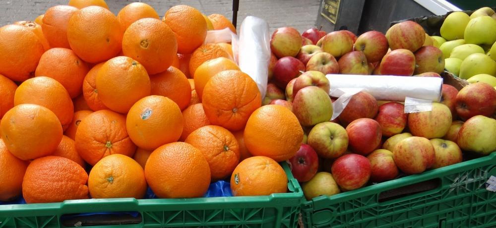 Apelsiner och äpplen i gröna plastlådor