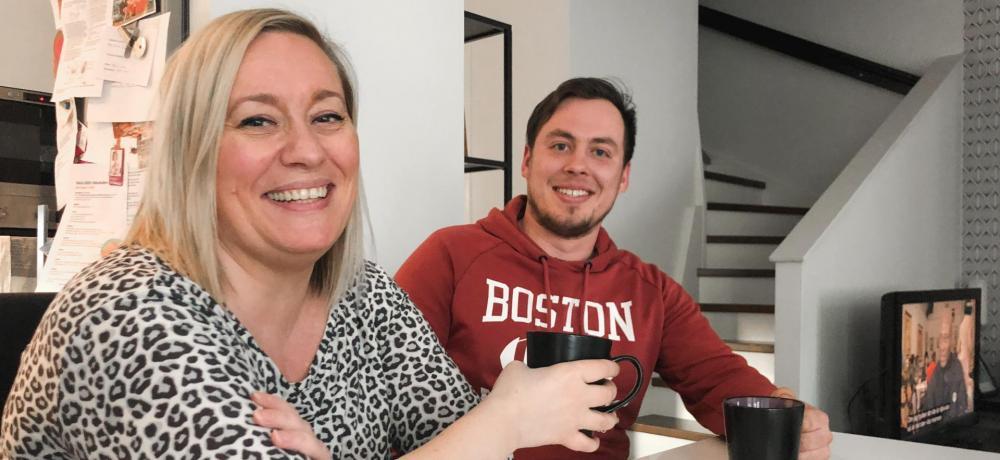 Anna och Jonatan ler in i kameran med kaffekopp i handen.