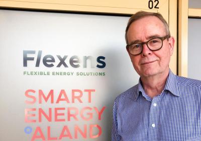 Berndt Schalin står framför skylten till Flexens och Smart Energy Ålands kontor