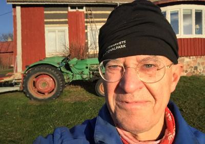 Bild på Christian med traktor i bakgrunden