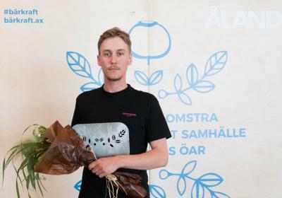 Fjolårets vinnare av bärkraft-priset, med blommor och pris i händerna