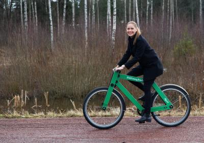 Kvinna cyklar på grön cykel