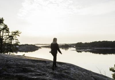 Person på ett berg som ser ut över vattnet