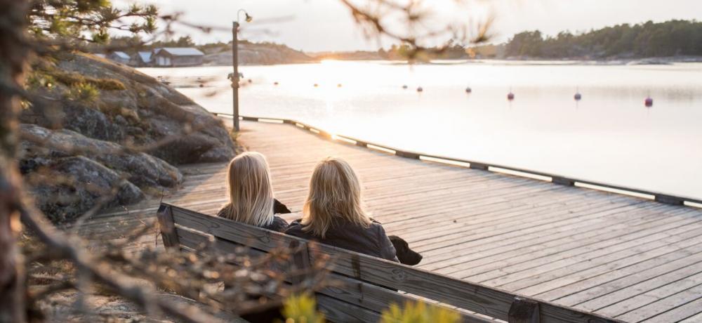 Två personer på bänk vid brygga som ser ut över havet