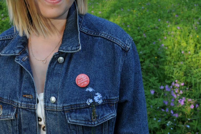 Kvinna i jeansjacka med röd alla kan blomstra pin.