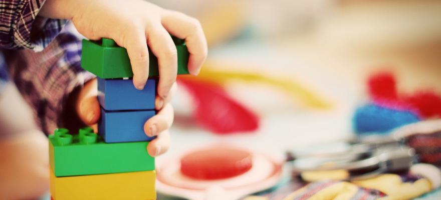 Barnhand som bygger lego
