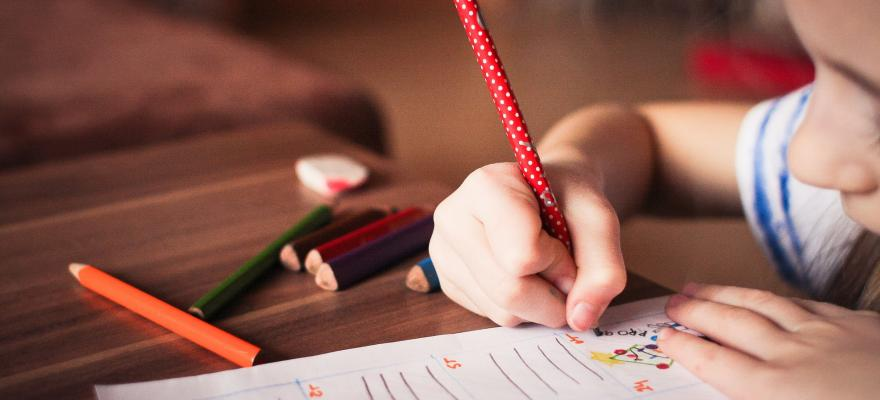 Bild på barn med en penna i handen