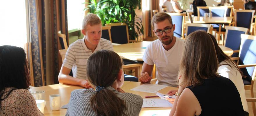 Ungdomar sitter runt ett bord och arbetar