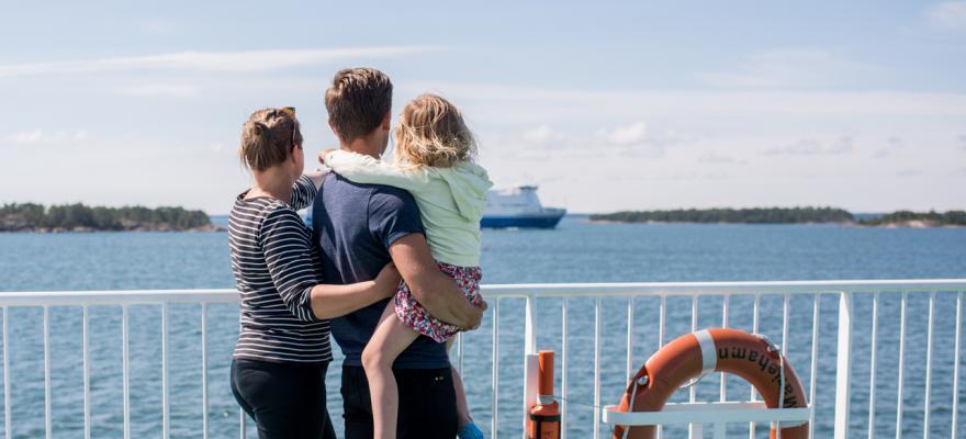 Familj som åker färja och tittar ut över vattnet