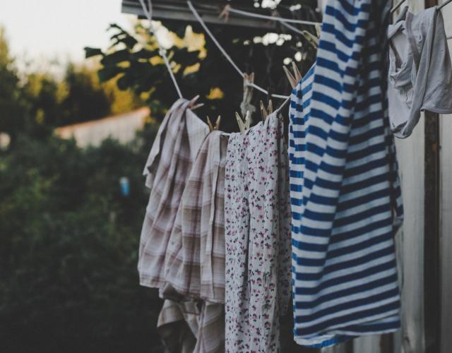 Tvätt upphängd med klädnypor på klädstreck utomhus.