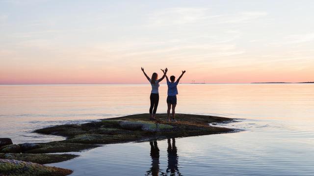 Människor i solnedgången en stilla kväll vid havet.