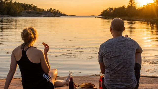 Två personer sitter på ett berg vid vattnet